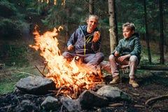 父亲和儿子在营火的烘烤蛋白软糖 免版税库存照片