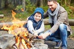 父亲和儿子在营火的烧烤蛋白软糖 免版税库存照片
