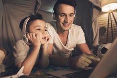 父亲和儿子在skype在家谈话与在膝上型计算机的家庭在晚上 库存照片