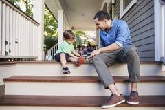 父亲和儿子坐一起使用与玩具的议院门廊 库存图片