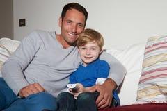 父亲和儿子坐一起看电视的沙发 免版税库存图片