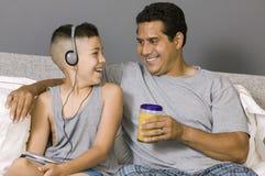 父亲和儿子坐听到音乐的床 免版税库存图片