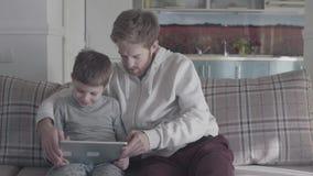 父亲和儿子坐在片剂的长沙发在大客厅和戏剧 爸爸教他的孩子 愉快的家庭花费 股票视频