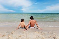 父亲和儿子坐沙滩。 库存图片