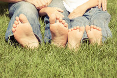 父亲和儿子坐草在天时间 库存图片