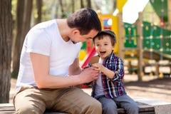 父亲和儿子坐长凳并且吃冰淇淋在公园在晴朗的春天或夏日 获得的父亲和的儿子乐趣一起 免版税库存图片