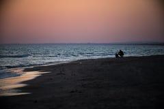 父亲和儿子坐靠近海在日落 免版税图库摄影