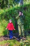父亲和儿子夏天钓鱼的 图库摄影
