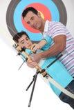 父亲和儿子实践的射箭 免版税库存图片