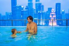 父亲和儿子室外游泳池的有城市视图在蓝色s 免版税库存图片