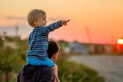 父亲和儿子室外画象在日落阳光下 图库摄影