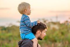 父亲和儿子室外画象在日落阳光下 免版税库存照片