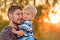 父亲和儿子室外画象在日落阳光下 免版税库存图片