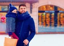 父亲和儿子寒假购物的在城市,购买礼物 免版税库存照片