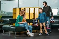 父亲和儿子带来了家庭的溜冰鞋 免版税库存图片