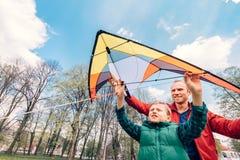 父亲和儿子开始飞行在天空的一只风筝 图库摄影