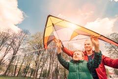 父亲和儿子开始飞行在天空的一只风筝 库存图片