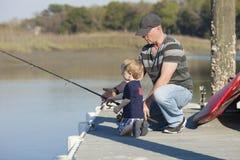 父亲和儿子捕鱼 免版税库存图片