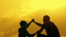 父亲和儿子握手在协议的 愉快的家庭获得乐趣在晚上美好的自然风景