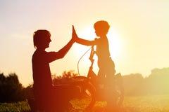 父亲和儿子有乐趣骑马自行车在日落 免版税库存照片