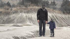 父亲和儿子有握手的防毒面具的在一个使荒凉的地方 股票录像