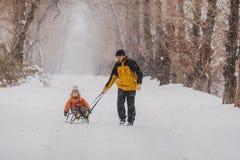 父亲和儿子有爬犁的室外在雪 库存照片