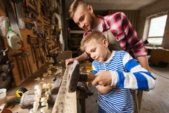父亲和儿子有运转在车间的锤子的 免版税库存照片