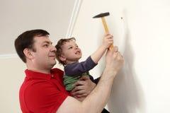 父亲和儿子有锤子的 免版税库存图片