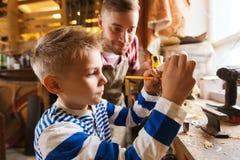 父亲和儿子有统治者的在车间测量木头 免版税库存图片