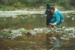 父亲和儿子步行和一起使用 在山的秋天 免版税库存图片