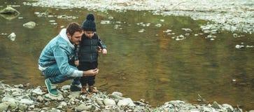 父亲和儿子步行和一起使用 在山的秋天 免版税库存照片