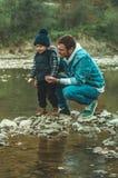 父亲和儿子步行和一起使用 在山的秋天 库存图片
