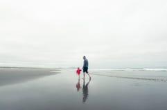 父亲和儿子海滩的在冬天 免版税库存图片