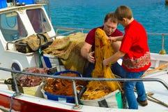 父亲和儿子清洁捕鱼网 免版税库存图片