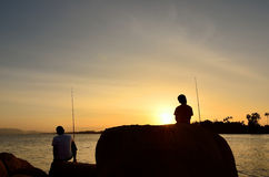 父亲和儿子渔剪影在海洋 免版税图库摄影