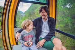 父亲和儿子滑雪电缆车客舱的在夏天 cabl的乘客 免版税库存照片