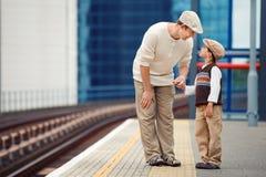 年轻父亲和儿子火车站平台的 免版税库存照片