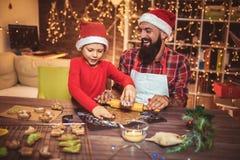 父亲和儿子烘烤姜饼圣诞节曲奇饼 库存图片