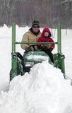 父亲和儿子犁在拖拉机的多雪的驱动 免版税库存照片