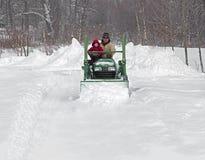 父亲和儿子犁在拖拉机的多雪的驱动 免版税图库摄影