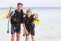 父亲和儿子用佩戴水肺的潜水设备海滩假日 免版税库存照片