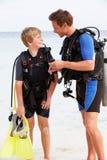 父亲和儿子用佩戴水肺的潜水设备海滩假日 库存照片