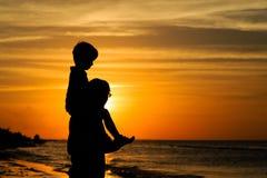 父亲和儿子看日落的肩膀的 免版税库存照片