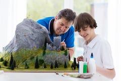 父亲和儿子研究建立模型项目 免版税库存照片