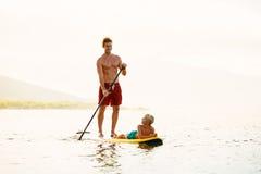 父亲和儿子站立用浆划 免版税库存图片