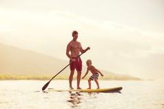 父亲和儿子站立用浆划 免版税库存照片
