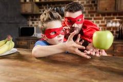 父亲和儿子红色超级英雄的打扮使用用苹果 免版税库存图片