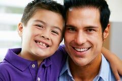 父亲和儿子纵向在家坐沙发 免版税库存图片