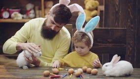 父亲和儿子绘复活节彩蛋 逗人喜爱的小孩男孩佩带的兔宝宝耳朵 在木背景的复活节彩蛋 人 股票录像