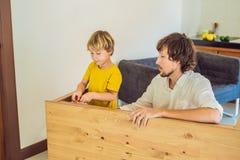 父亲和儿子聚集的家具 在家帮助他的爸爸的男孩 愉快概念的系列 库存照片